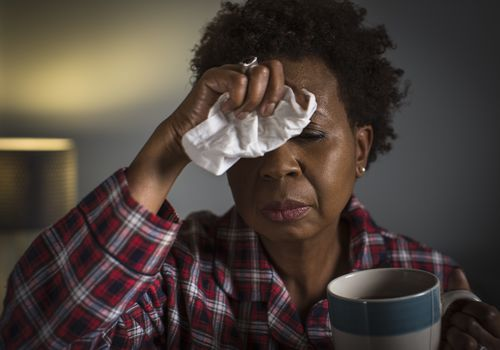 Mature woman with cold touching forehead
