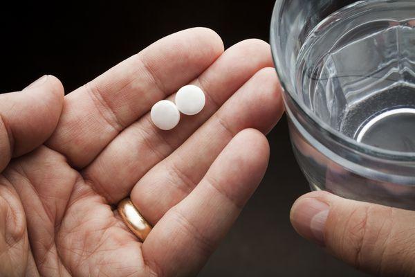 Man holding aspirin pills