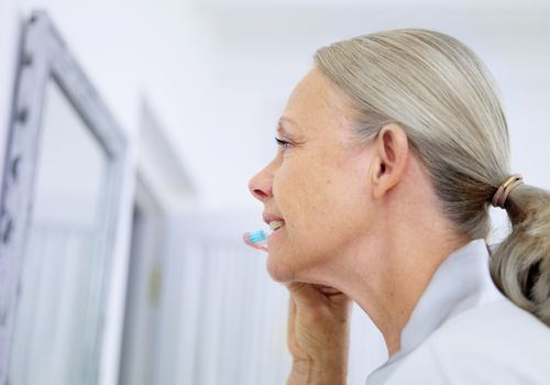 senior woman brushing teeth