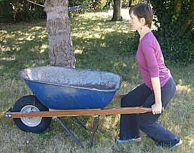 Bend down to grasp the weight of the wheelbarrow from underneath.