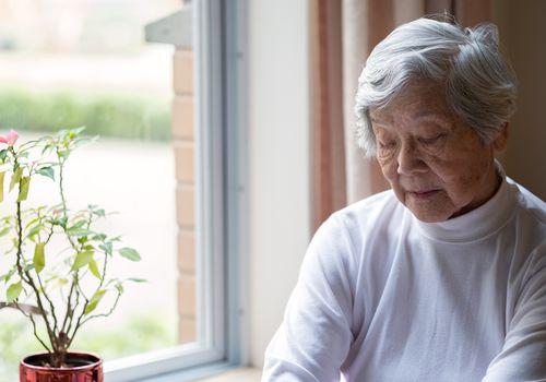 Senior woman sitting by window
