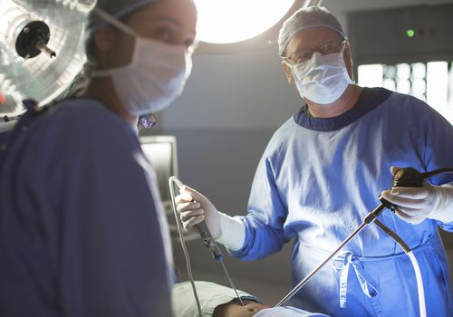Two doctors performing laparoscopic surgery