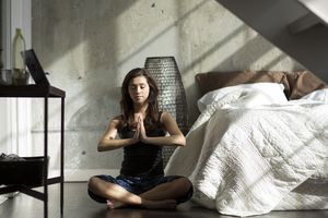 Woman practicing yoga on bedroom floor