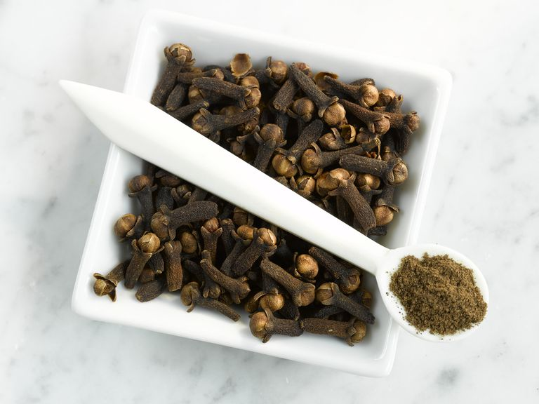 Cloves and clove powder in a porcelain dish