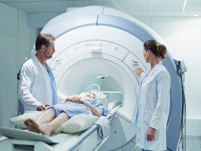 Doctors preparing patient for MRI scan