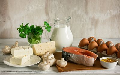 An array of vitamin-D-rich foods, such as milk, cheese, eggs, salmon, and mushrooms.