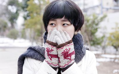 young woman with cold hands due to Raynaud's syndrome
