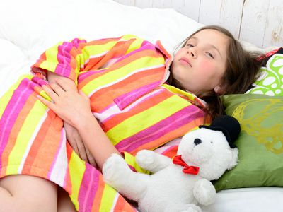 Girl Holding Stomach While Lying On Bed