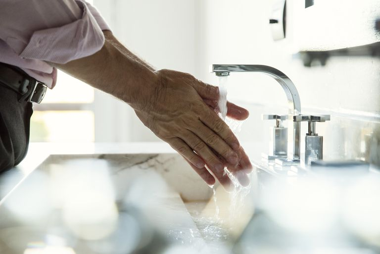 Man washing hands in bathroom sink, cropped