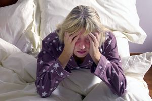 woman looking distressed in bed