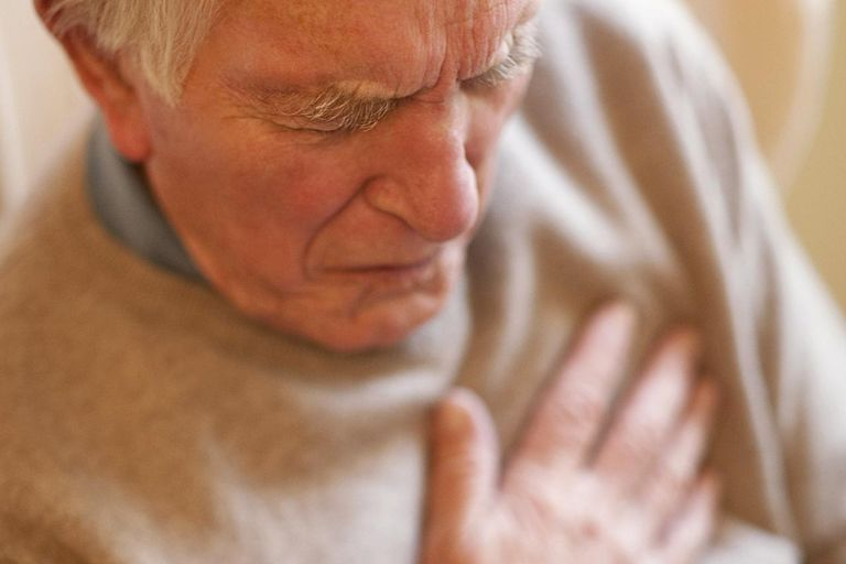 Senior man clutching at his chest in pain while suffering a heart attack.