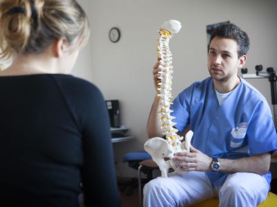 Young male doctor holding model spine in front of blonde woman with her back to the camera