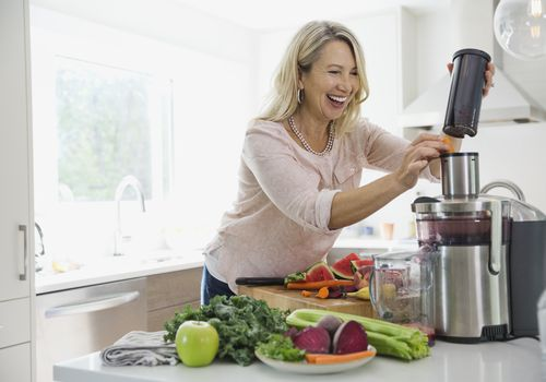 Happy woman putting carrots in juicer