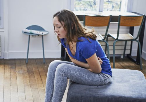 Woman with abdominal pain sitting on the footrest