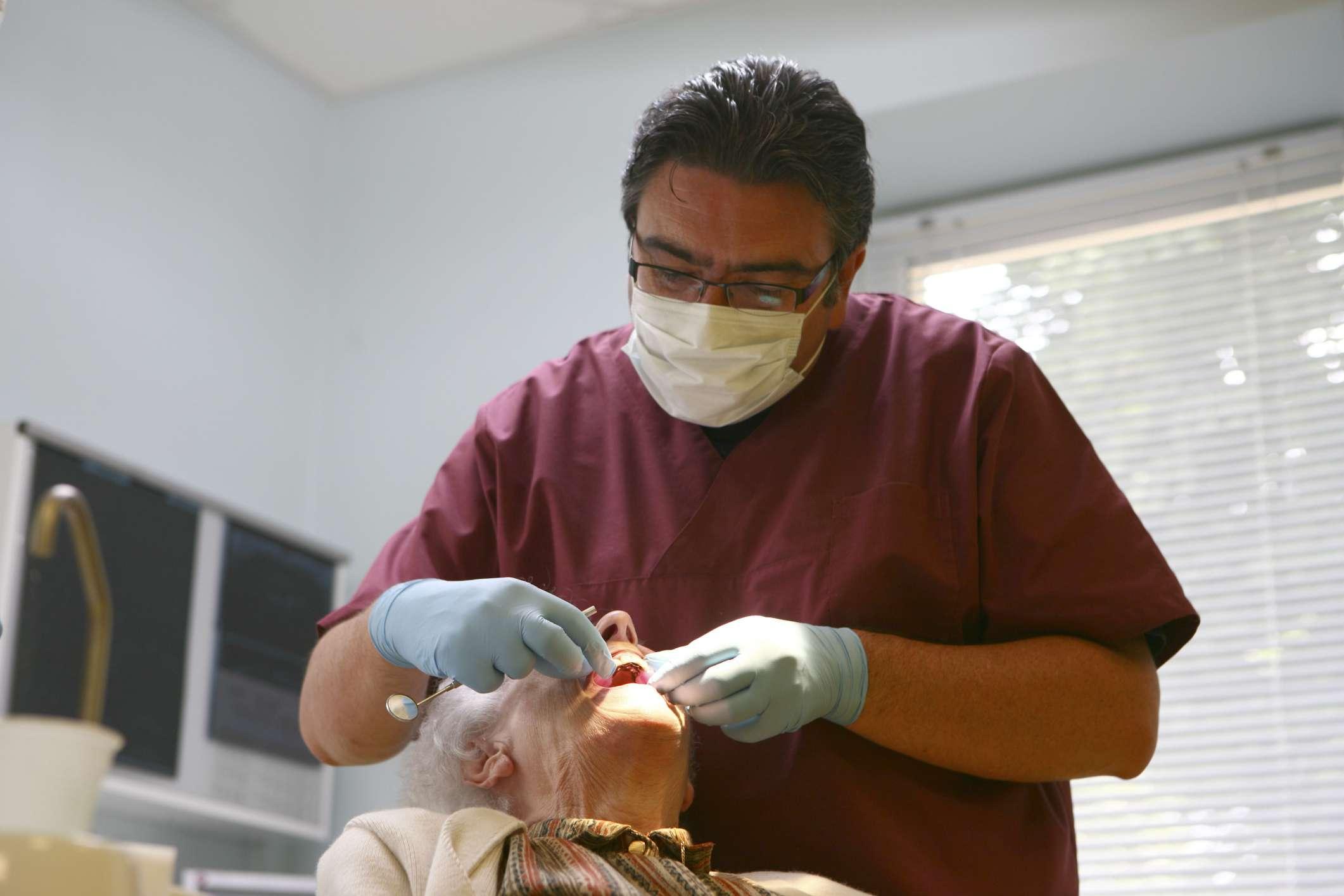 Dentist working on older woman