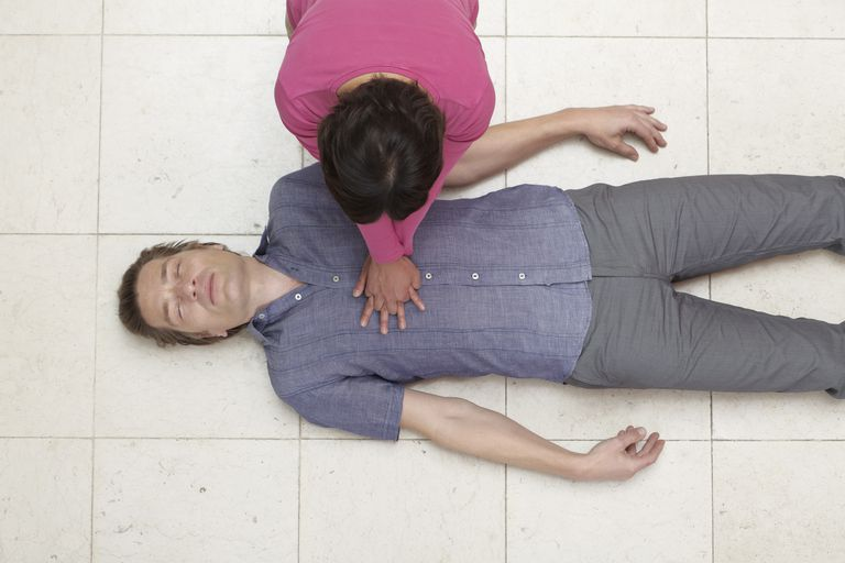 woman doing CPR on a man, overhead shot