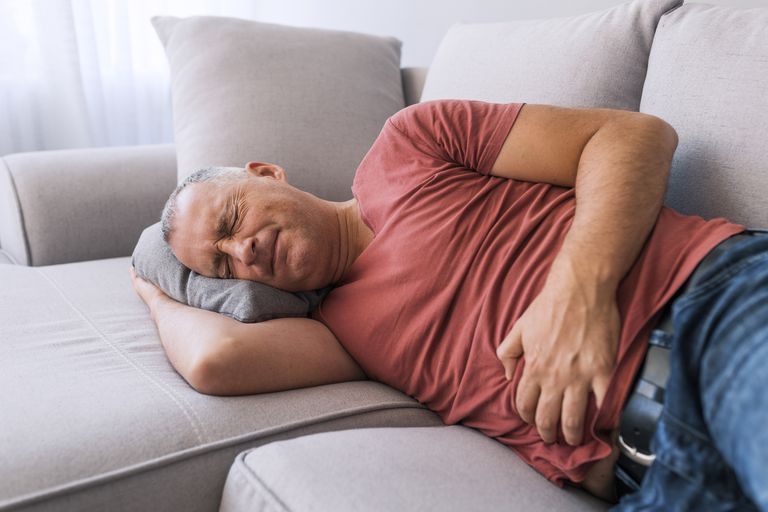 Man laying on the couch with stomach