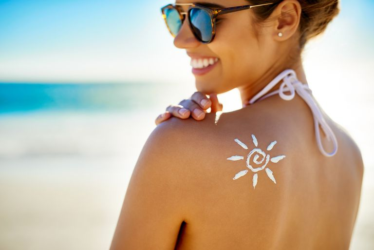 Woman at the beach with a sun drawn on her back with sunscreen
