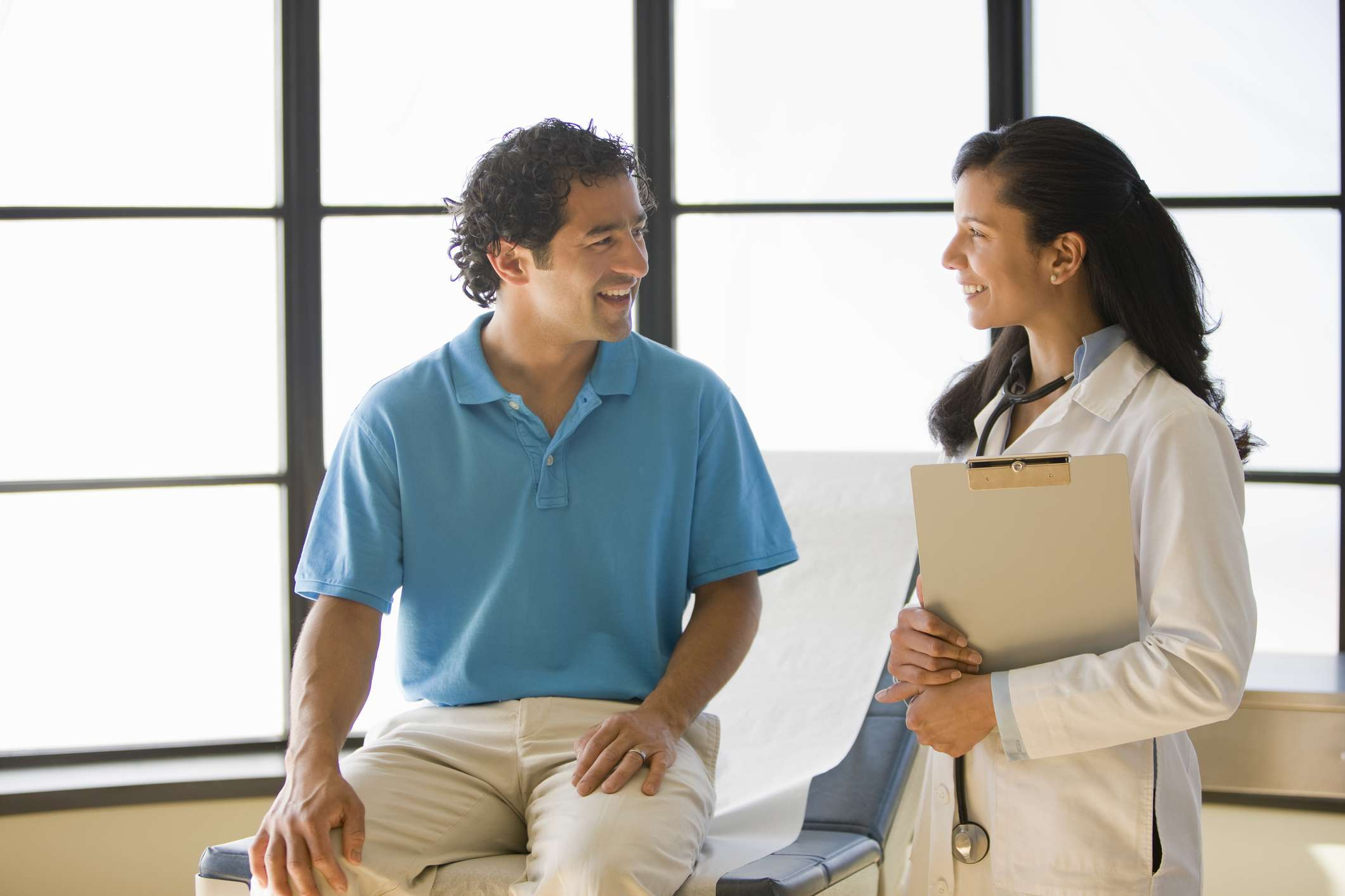 Female doctor talking with male patient, both smiling
