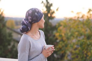 Cancer patient outside holding coffee cup and looking at the sunrise.