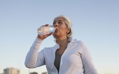 Mature woman walking while drinking water