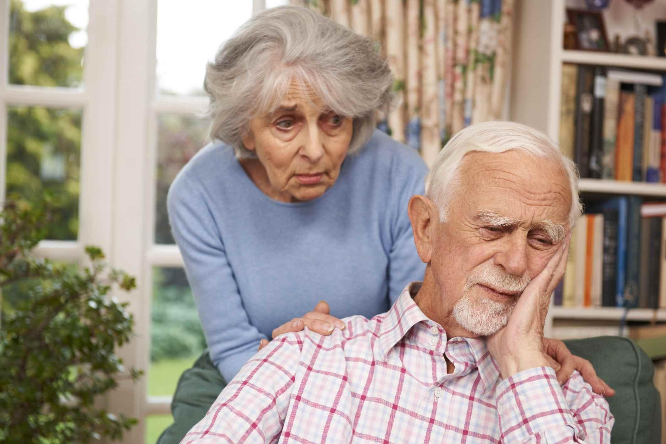 Sad senior man with concerned senior woman