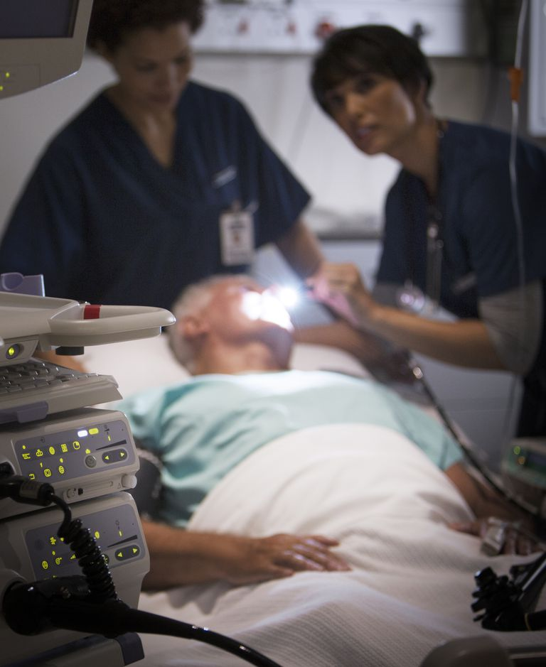 Doctor examining senior patient with flashlight in intensive care unit