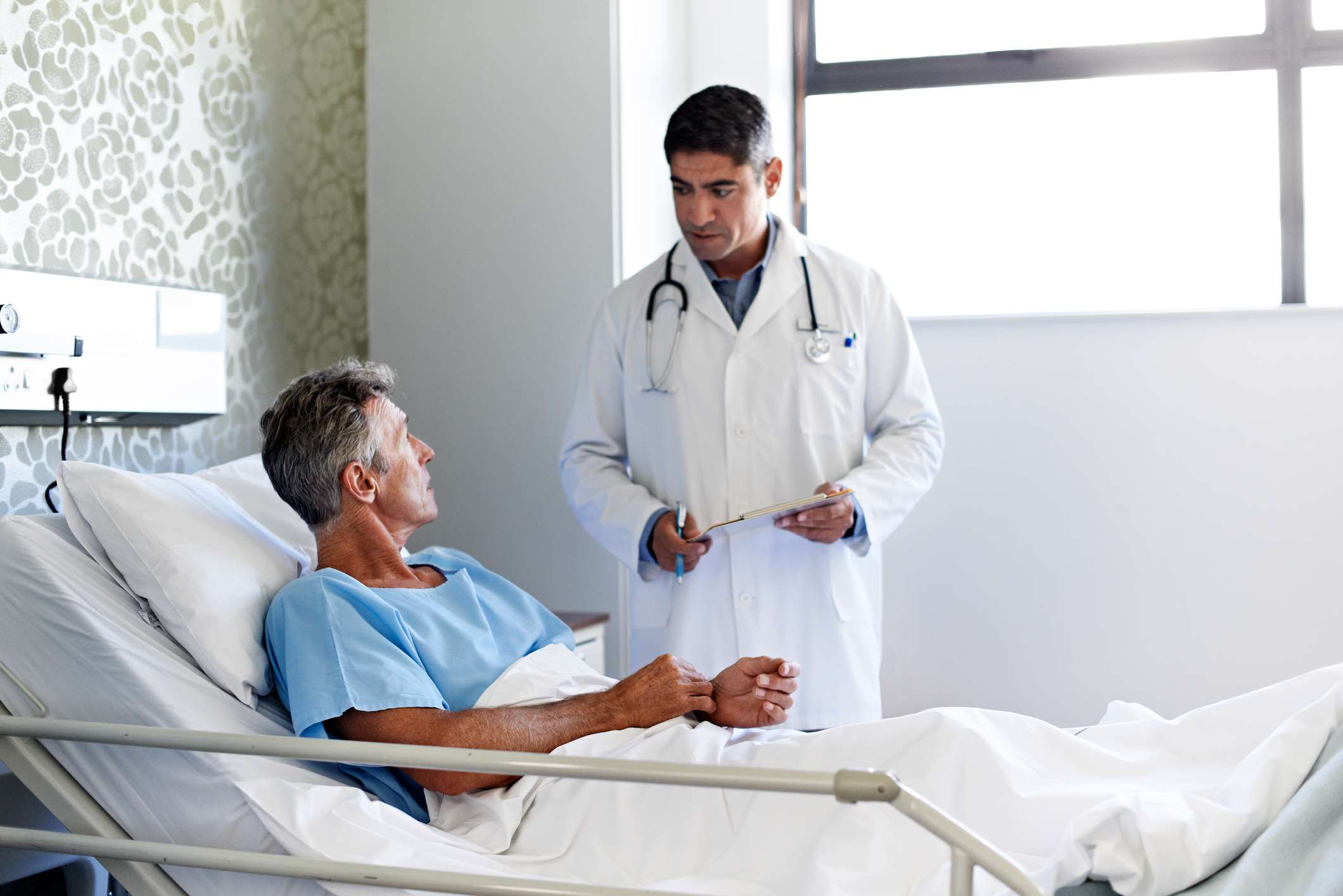 A man and his doctor talking in a hospital room
