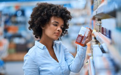 A woman looking medicine in the pharmacy aisle