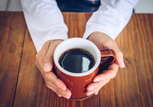 Someone hands holding a mug of black coffee before drinking.