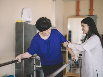physical therapist assisting elderly woman walking in parallel bars