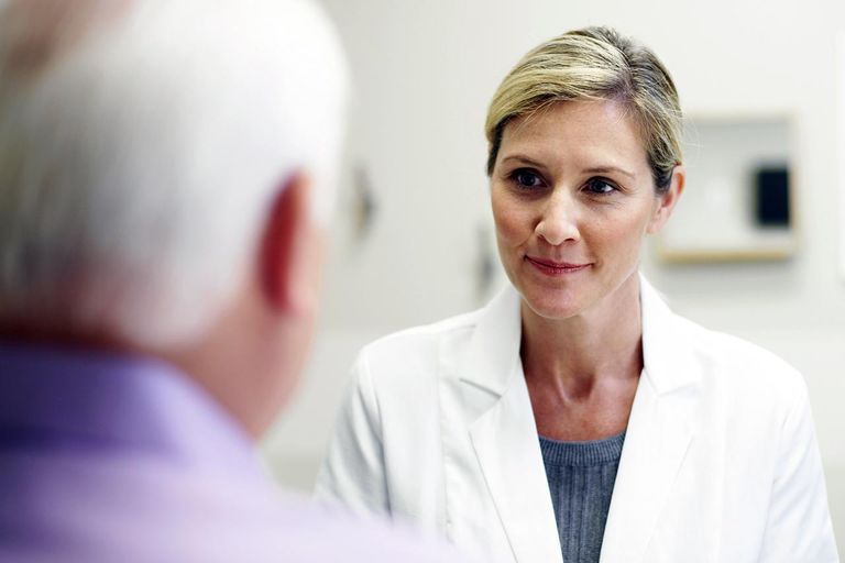 Female opthamologist listening to a patient in an exam room