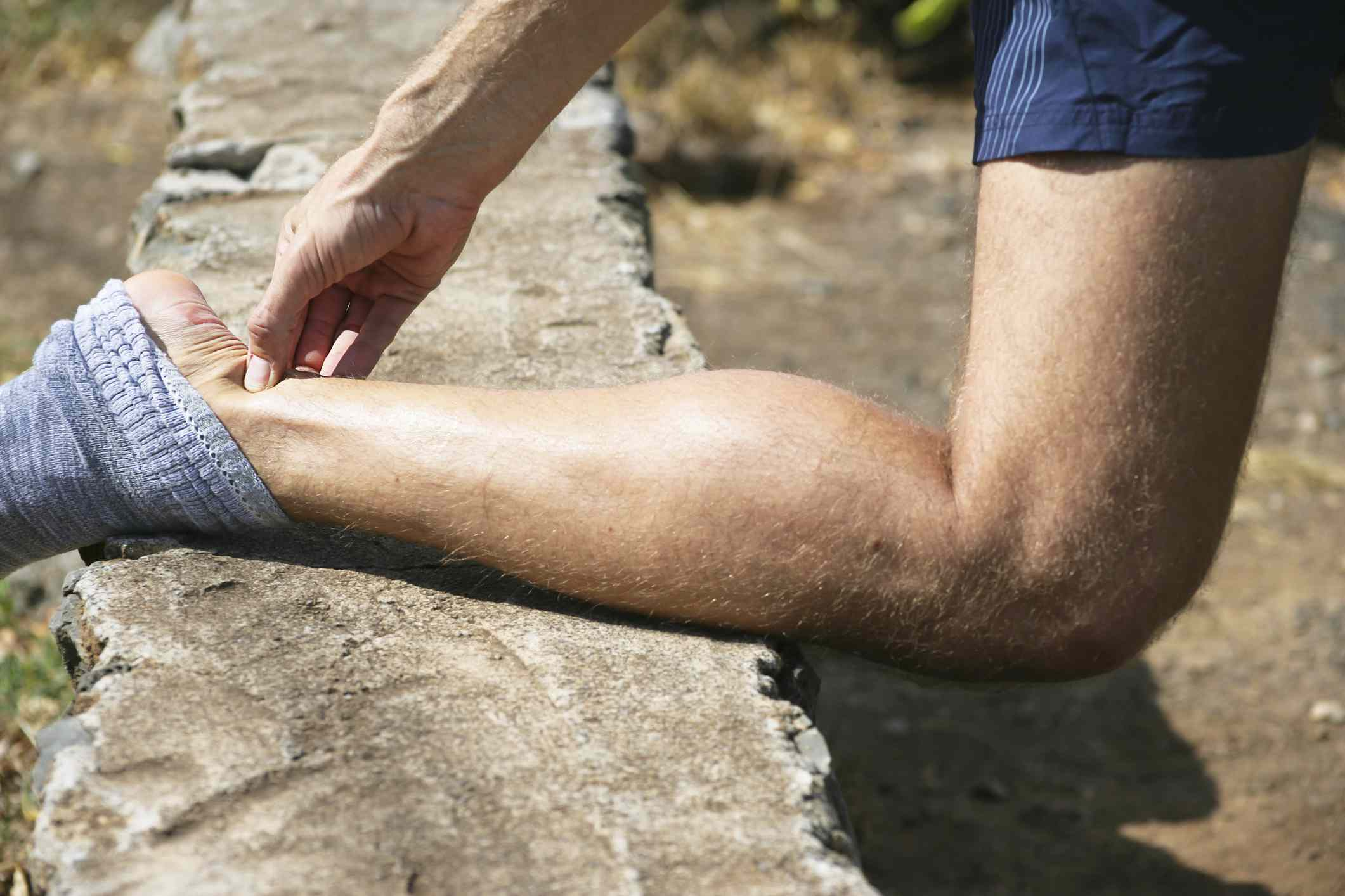 A runner holding his Achilles tendon