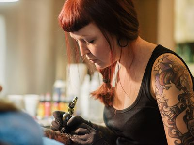 A female tattoo artist working on a customer