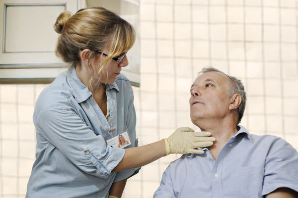 Healthcare worker checking man's throat