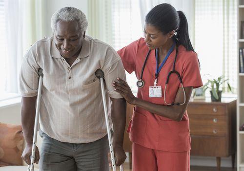 Female caregiver helping older man walk with crutches