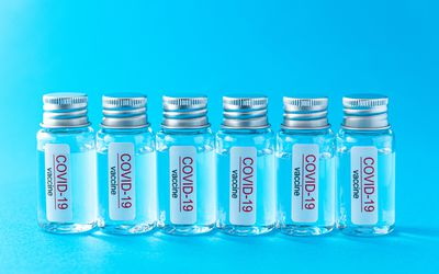 Six glass vials labeled COVID-19 vaccine on a bright blue background.
