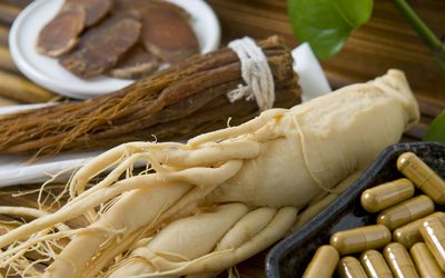 Close-up of dry ginseng slices, capsules and roots