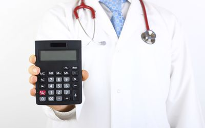 Doctor holding a calculator.