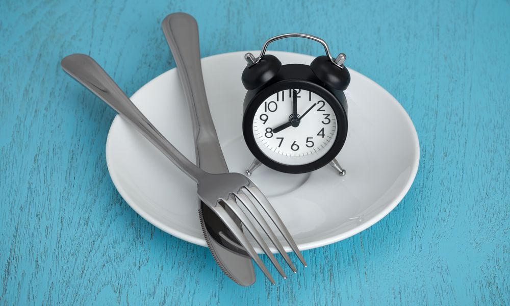 clock on an empty plate illustrating intermittent fasting for cancer