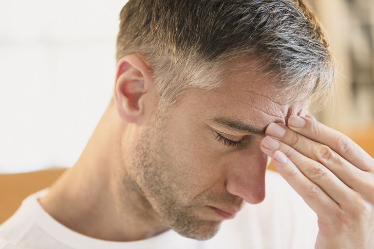 Close up of man with headache touching forehead