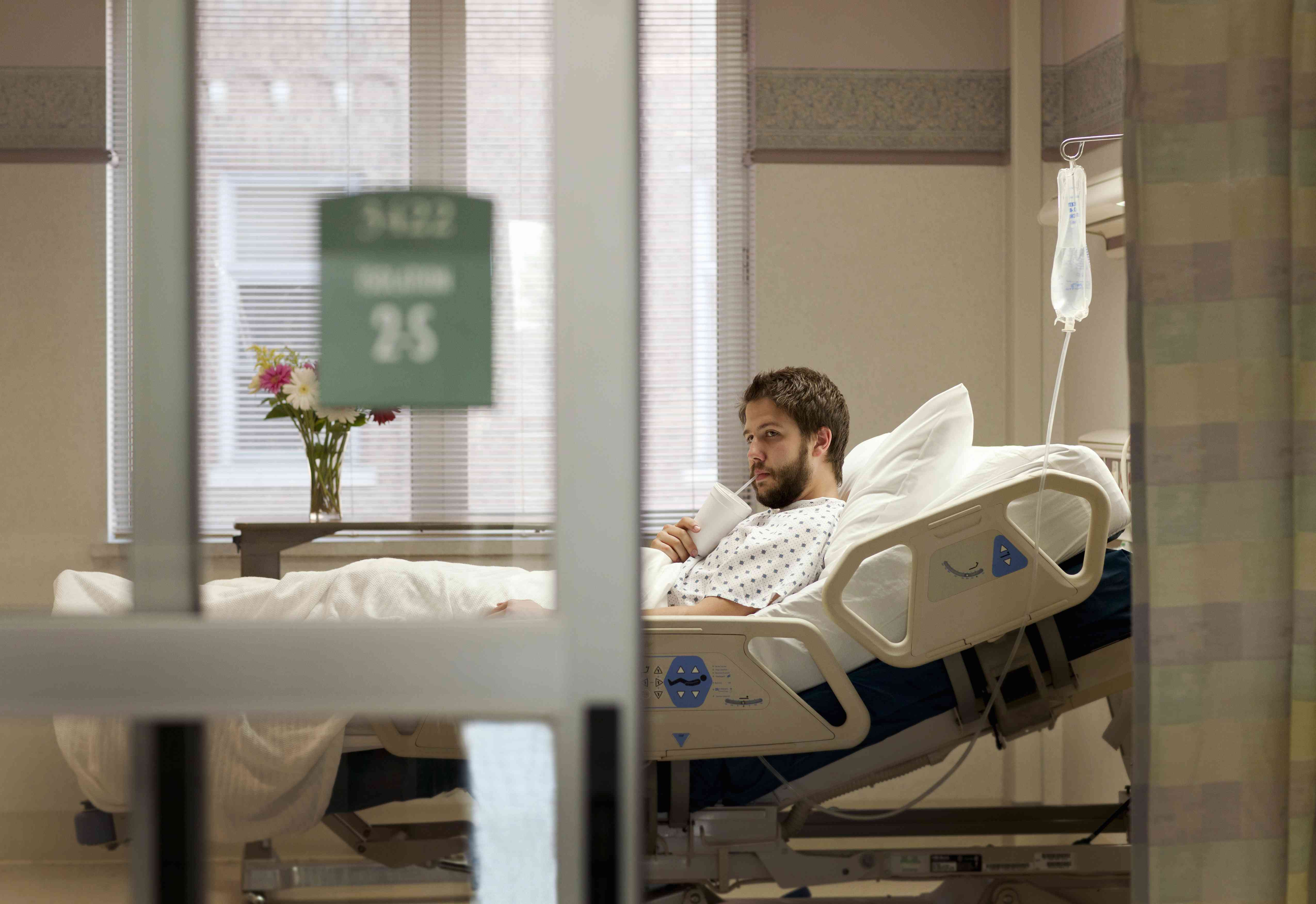Man drinking from cup in hospital bed