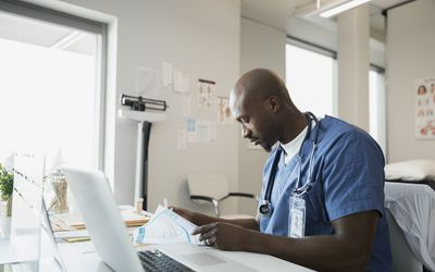 Doctor in scrubs reviewing paperwork in clinic office