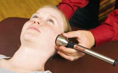 Doctor Administering Cold Laser Therapy Treatment to Female Pati