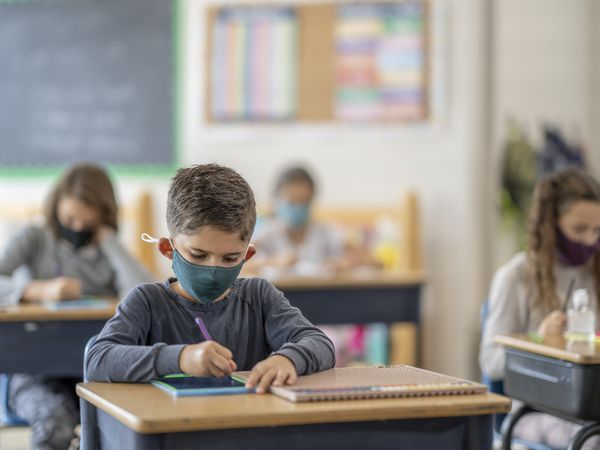 Children in school with masks, socially distanced