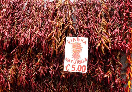 Red chili peppers hanging on the wall are promoted as natural Viagra in the village market on October 22, 2015 in Amalfi, Italy.