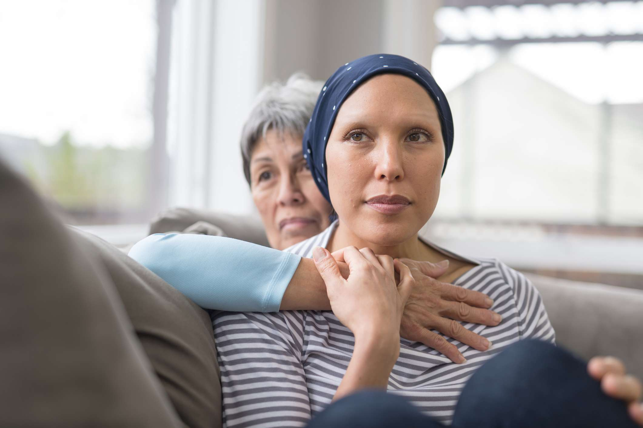Asian woman in 60s embracing her mid-30s daughter who is fighting cancer and is wearing a headcovering. They are seated on a couch and have contemplative expressions.
