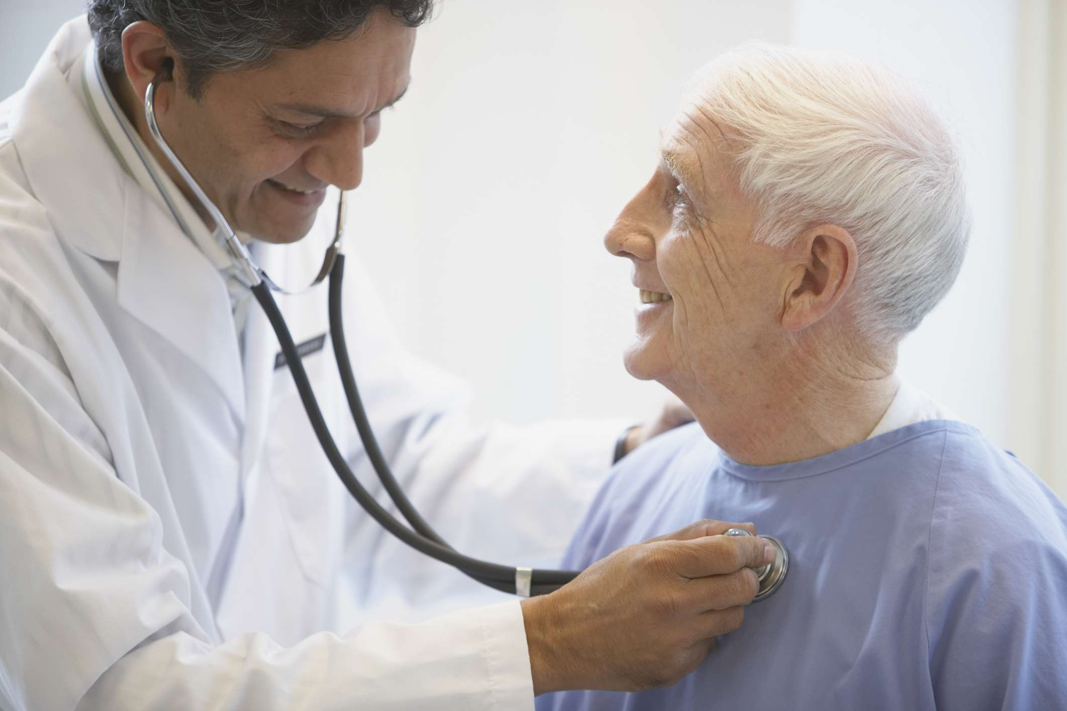 A doctor listening to the heartbeat of an older male patient