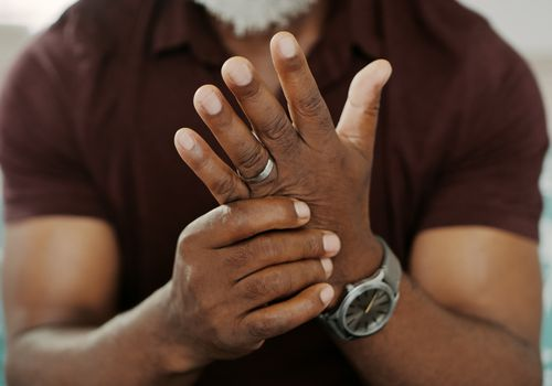 A man sits, holding one of his hands. He rubs one hand with his other, as though trying to relieve pain in his hand.