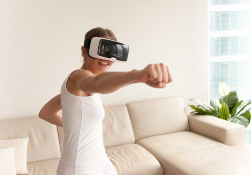 woman punching the air while using a VR headset
